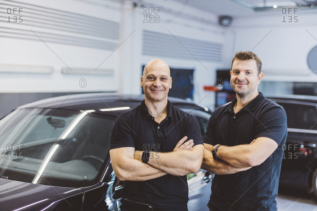 Portrait of confident male workers with arms crossed standing by car in workshop