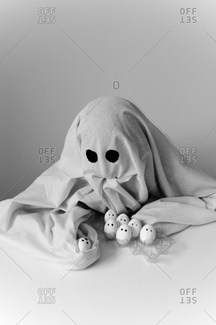 High angle view of man in ghost costume holding egg carton on table while sitting against wall during Halloween
