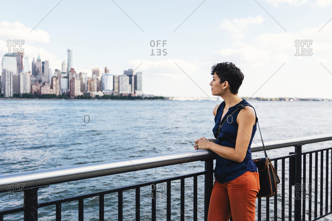 Side view of thoughtful woman looking away while standing on promenade by river against sky in city
