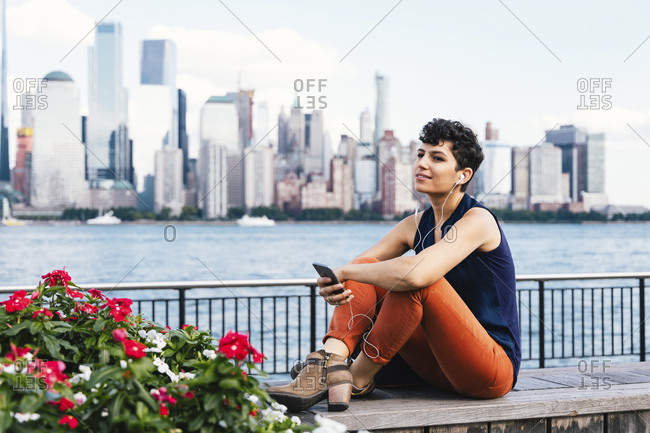 Woman listening music while sitting on retaining wall by river against buildings in city