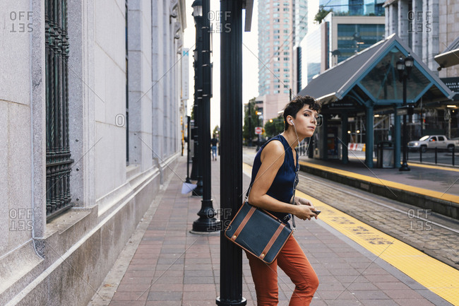 Side view of woman listening music while standing at railroad station platform