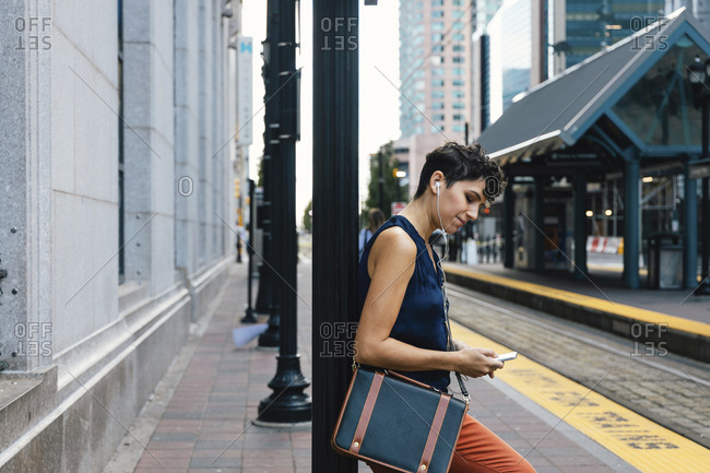 Side view of woman using mobile phone while listening music at railroad station platform