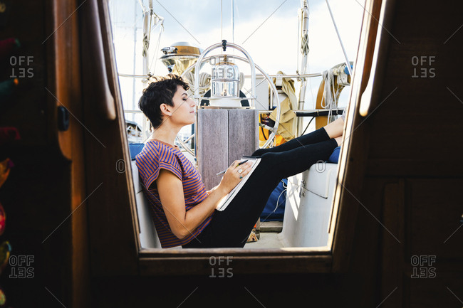 Side view of woman writing while sitting in boat against sky seen through window