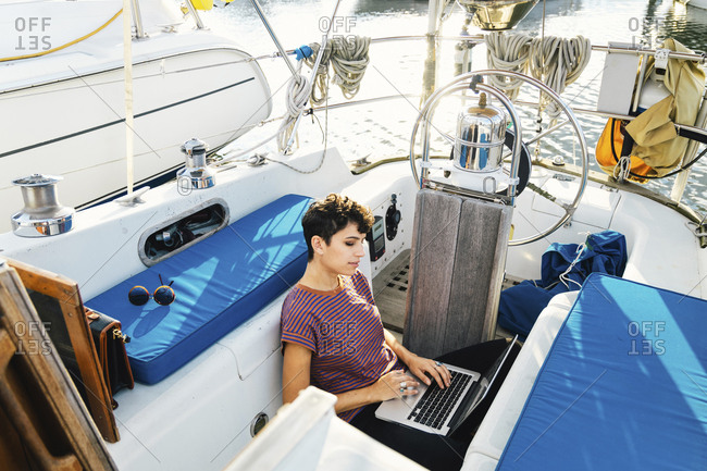 High angle view of woman using laptop computer while sitting in boat