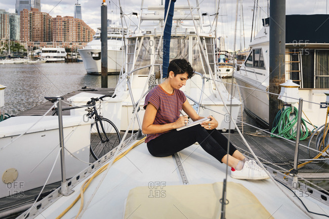 Side view of woman writing while sitting on boat against sky in city
