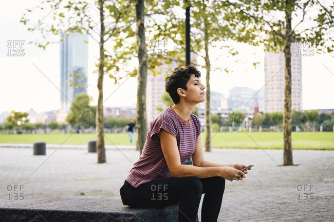 Side view of woman with eyes closed holding smart phone while sitting against sky in park