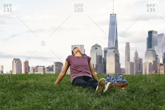 Woman relaxing while sitting on grassy field against cloudy sky in city
