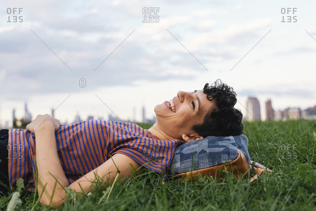 Side view of happy woman lying on grassy field against cloudy sky in city