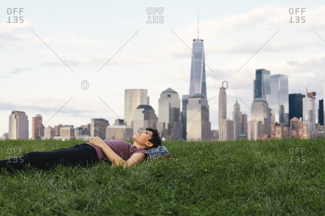 Thoughtful woman looking away while lying on grassy field against buildings in city