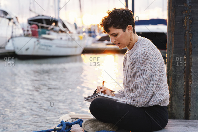 Side view of woman writing while sitting on pier at harbor against sky during sunset