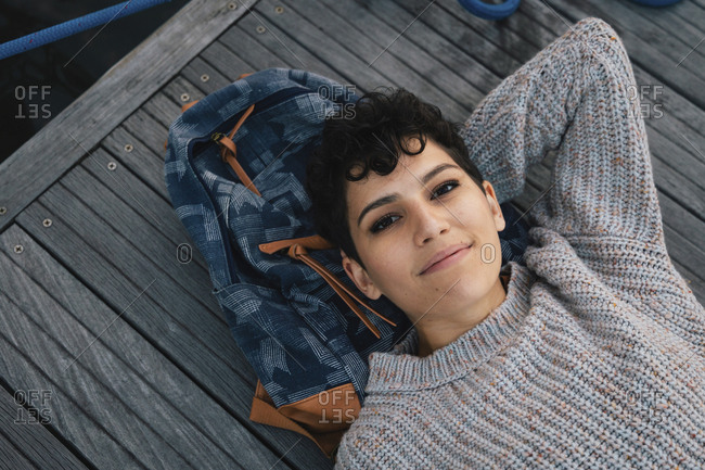 High angle portrait of smiling woman with backpack lying on pier at harbor during sunset
