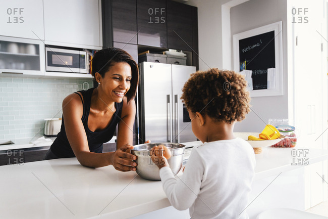 Smiling mother with son preparing food in kitchen at home