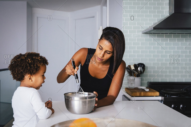 Son looking at mother preparing food on kitchen island