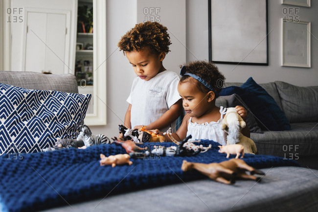Cute siblings playing with toys on sofa at home