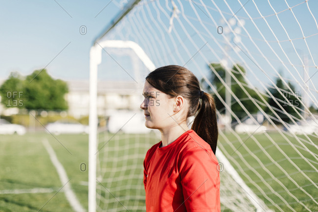 Girl looking away while standing by goal post on soccer field during sunny day