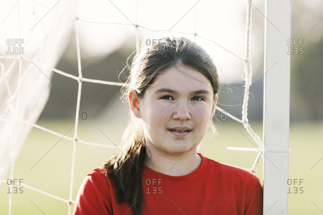 Portrait of confident soccer player wearing red uniform against goal post during sunny day