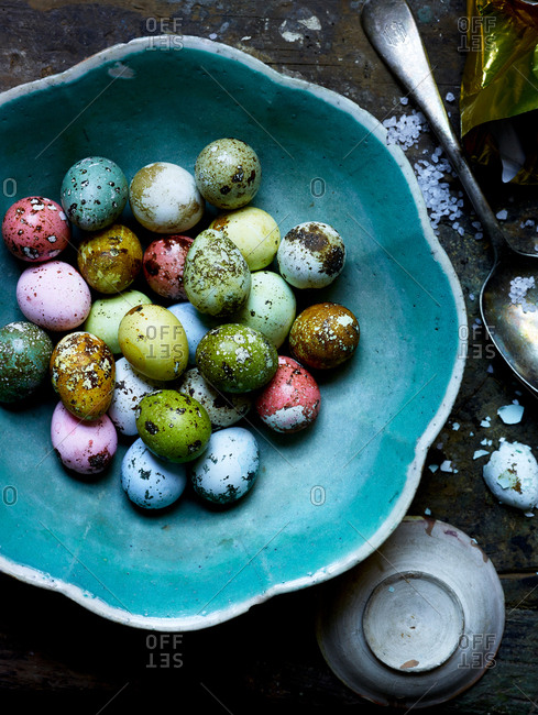 Colorful speckled Easter eggs in a blue bowl
