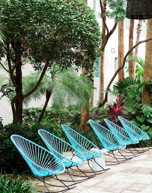 Blue rocking chairs on a tropical resort patio