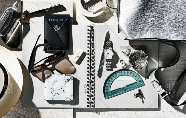 January 11, 2016: Overhead view of a cluttered desk with passport, office supplies, watch, and other items