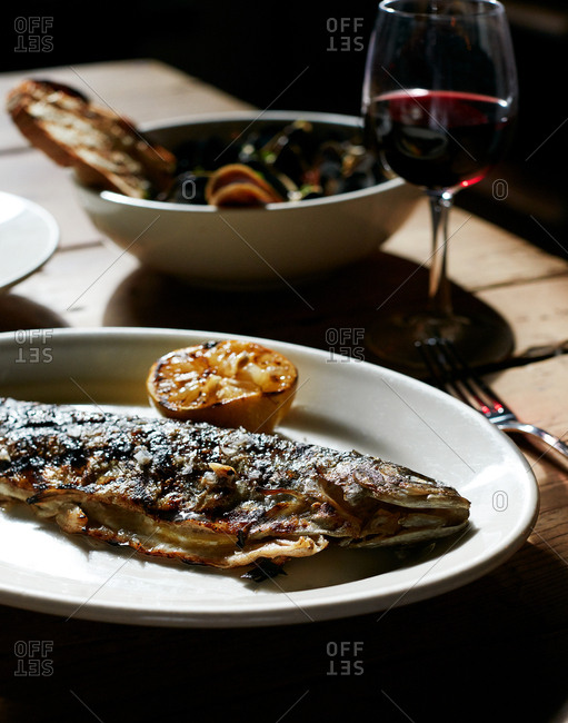 Whole grilled fish and lemon served with wine