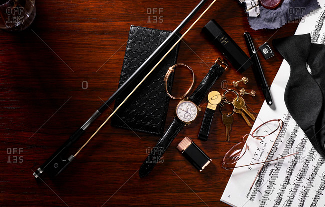 June 10, 2016: Overhead view of a cluttered desk with a high end watch, wallet, violin bow, and other items