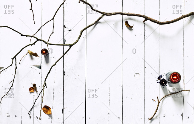 Branches on white painted wood and candles