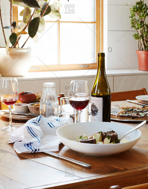 October 18, 2015: Beef dish on table with red wine