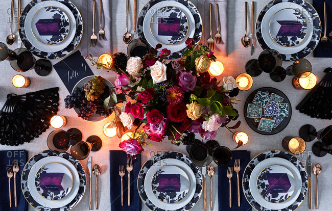 Overhead view of colorful flowers, place setting, and grapes on a wedding reception table
