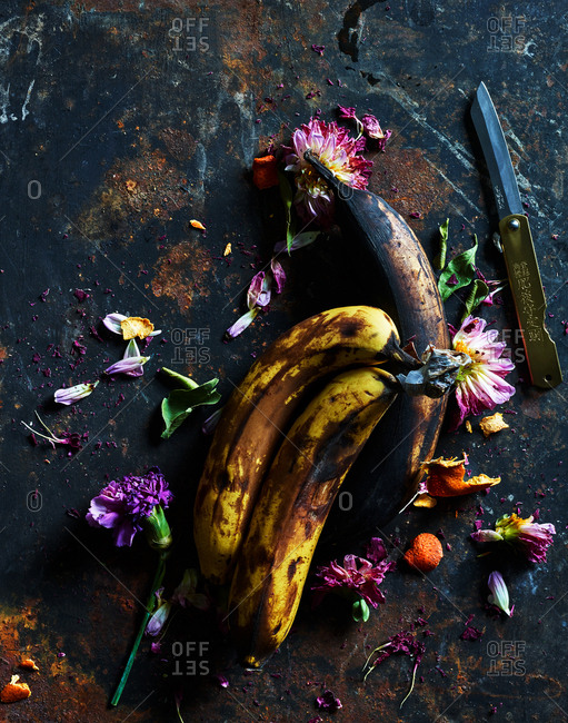 December 11, 2018: Bananas and flowers on rustic background