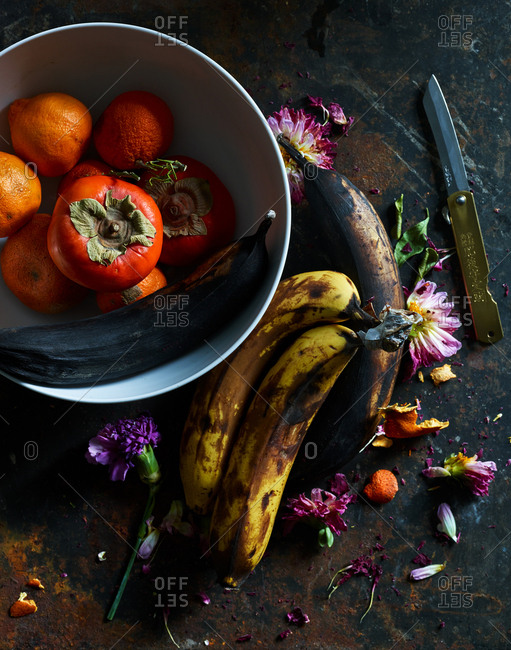 December 11, 2018: Fruit in a bowl and flowers on rustic background