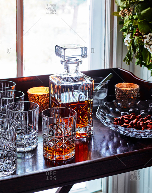 Liquor in a decanter and glass on a bar cart