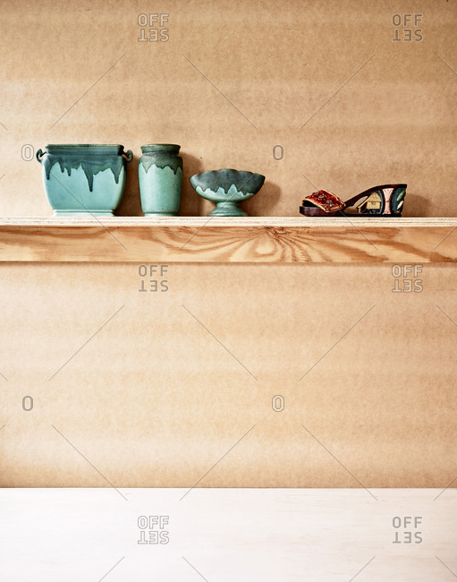 Wooden shelf with green pottery and a shoe