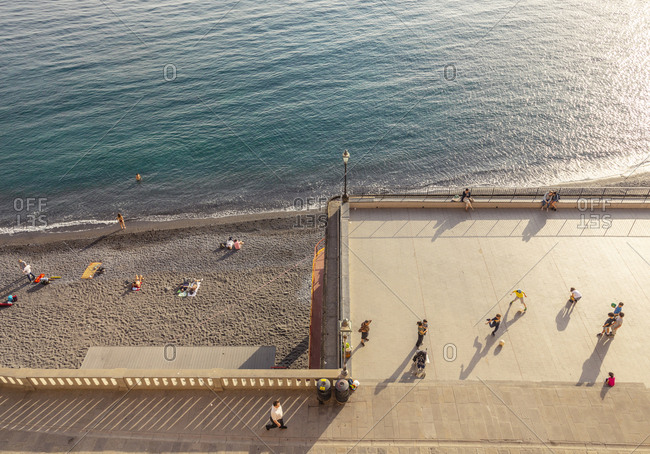 Camogli, Italy - April 23, 2018: People playing a ball game and relaxing by the beach