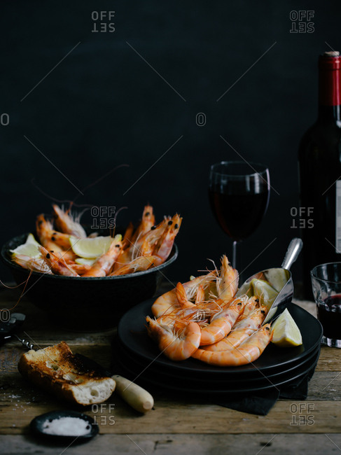 Bowls of boiled shrimp served with a toasted baguette