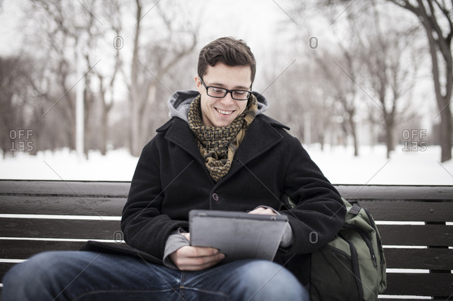 Young student outside in winter using tablet