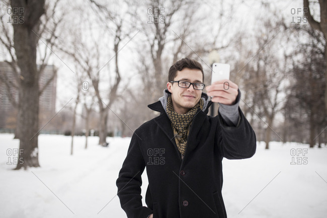 Young student outside in winter using smartphone