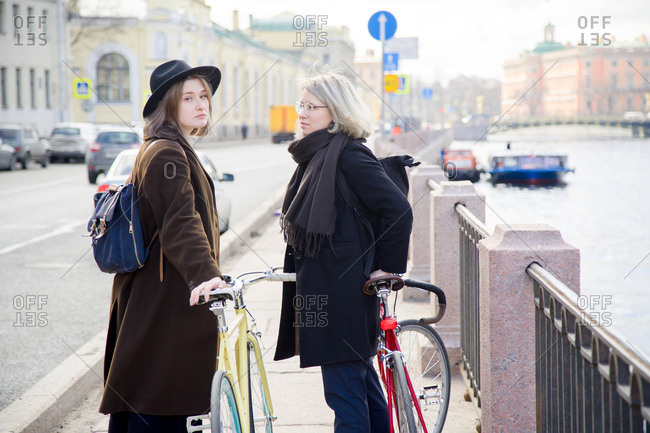 Female couple walking at the sunny city river embankment with bicycles