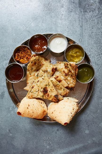 Indian appetizer dish with flatbread and dipping sauces