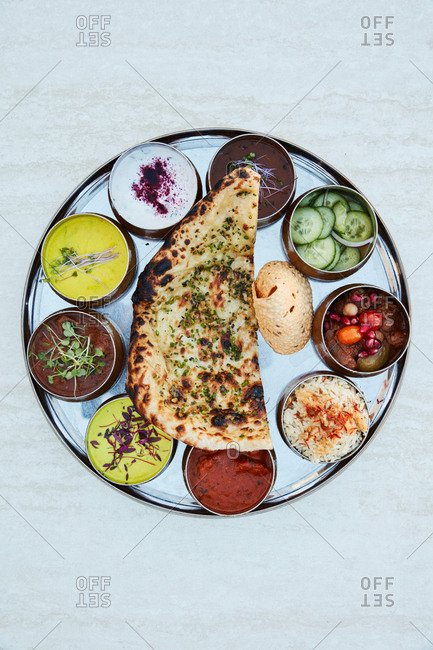 Indian appetizer dish with flatbread and various dipping sauces
