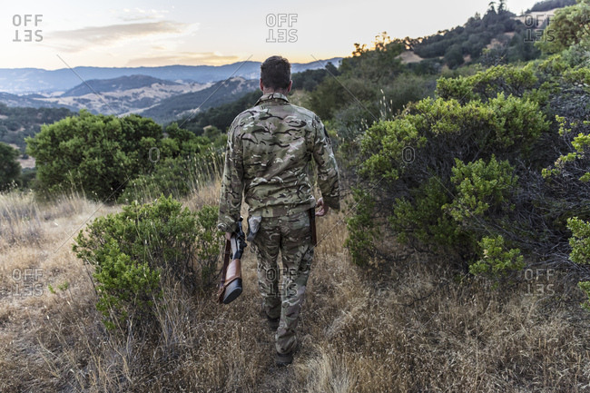 A hunter walks in the early morning looking to hunt wild pigs