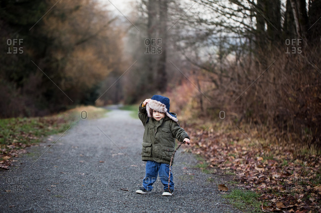Toddler boy walking in wood with a stick
