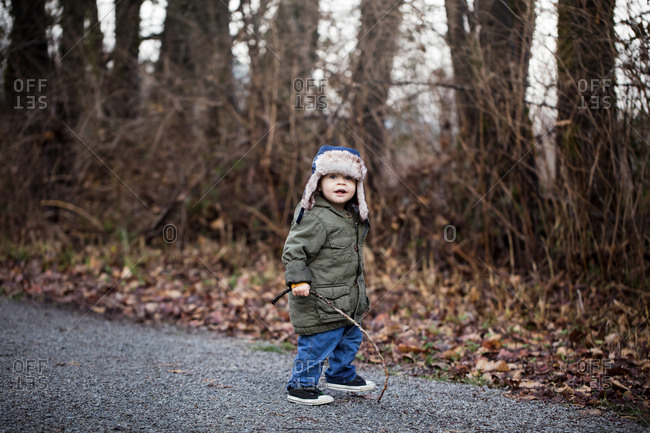 Cute toddler boy walking in wood with a stick