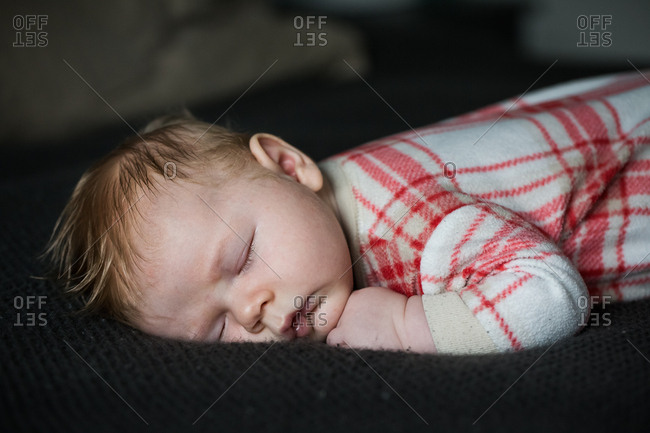 Sleeping newborn baby on black fuzzy blanket