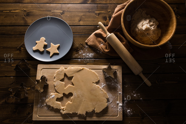 Christmas cookie dough being rolled and cutout on a wooden table