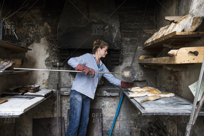Woman baking loaves of bread in an outdoor brick oven, Tuscany, Italy