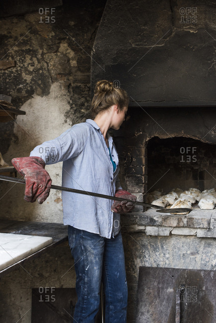 Woman removing loaves of bread from an outdoor brick oven, Tuscany, Italy
