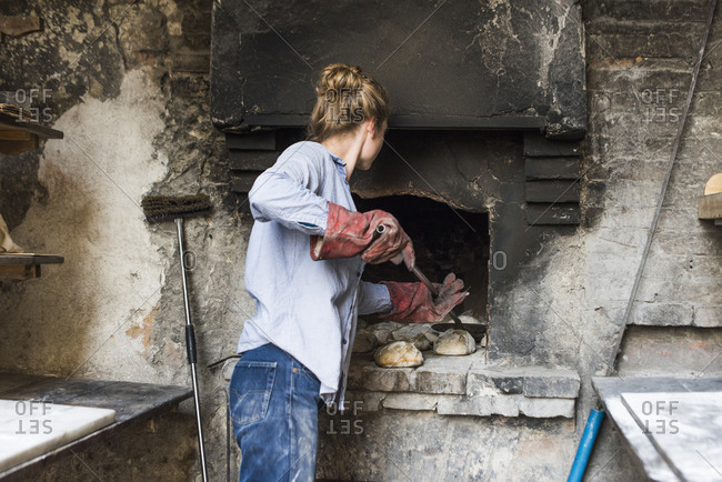 Woman removing bread from an outdoor brick oven, Tuscany, Italy