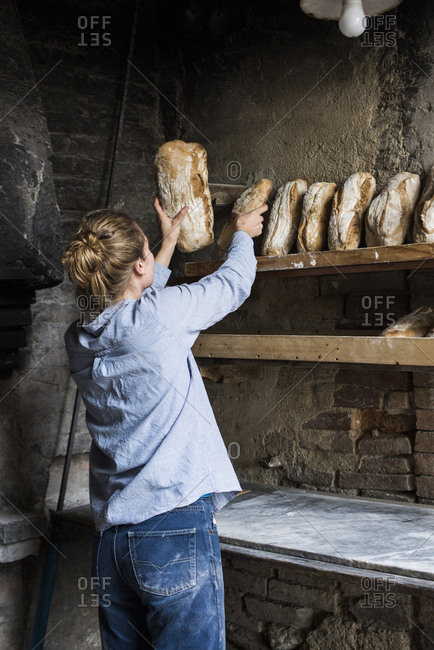 Young woman placing fresh baked loaves of bread on a shelf, Tuscany, Italy