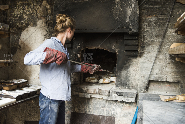 Young woman baking loaves of bread in an outdoor brick oven, Tuscany, Italy