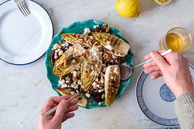 Person serving grilled endive and beetroot salad